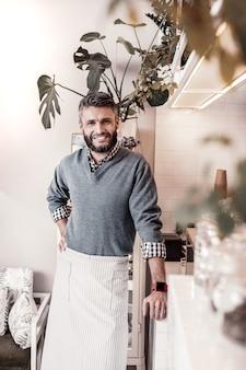 Pracownik kawiarni. wesoły przystojny mężczyzna uśmiecha się do ciebie, będąc gotowym do pracy