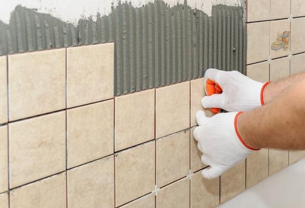 Pracownik kładzenie płytek na ścianie w kuchni.