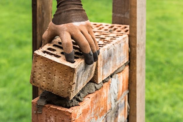 Pracownik kładzie cegły na zaprawie