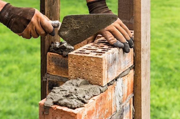 Pracownik kładzie cegły na zaprawie.