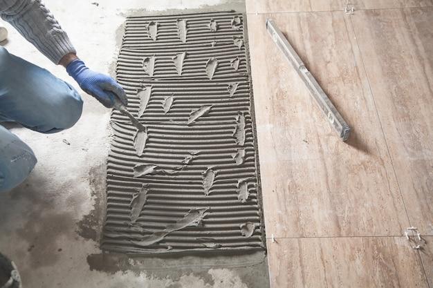 Pracownik kładzie na podłogę płytki klejące.