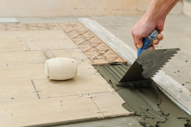 Pracownik kładzie płytki na podłodze.