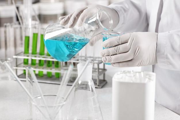 Pracownik kliniczny ubrany w białą fartuch i rękawiczki trzymając szklane zlewki z niebieskim płynem