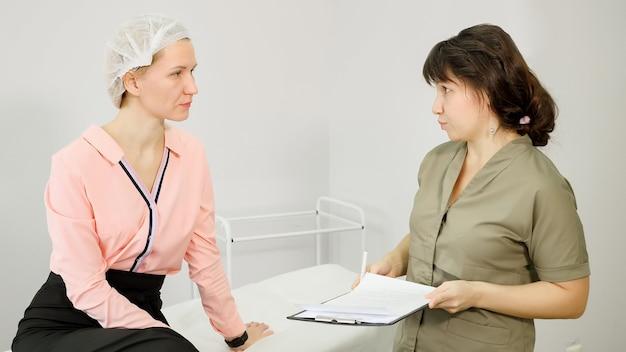 Pracownik kliniki urody w zielonym płaszczu konsultuje się z młodą kobietą
