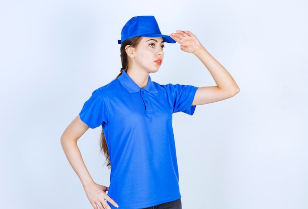 Pracownik kobieta dostawy w niebieskim mundurze stałego i pozowanie.