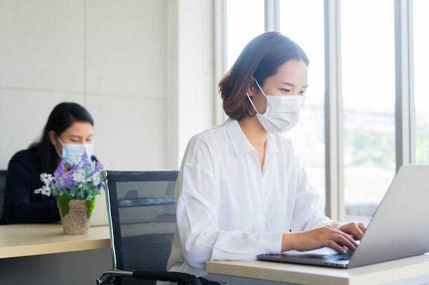 Pracownik kobieta siedzi na pulpicie i pisze na klawiaturze laptopa do pracy