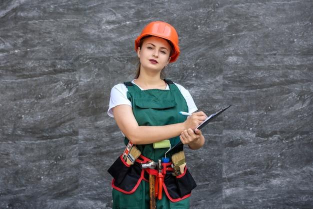 Pracownik kobieta w kombinezonie i hełmie pozowanie