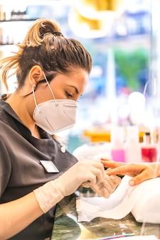 Pracownik kobieta z maską w leczeniu paznokci. ponowne otwarcie po pandemii coroda-19. salon manicure i pedicure. koronawirus