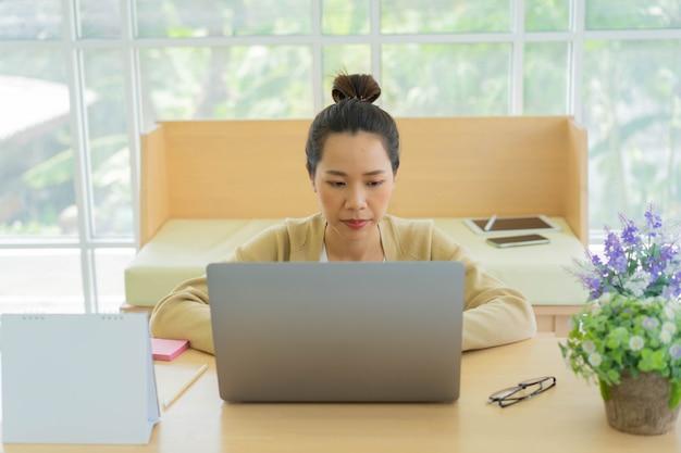 Pracownik kobieta za pomocą laptopa do sprawdzania poczty, zarządzania zadaniami i kontaktu z zespołem w salonie