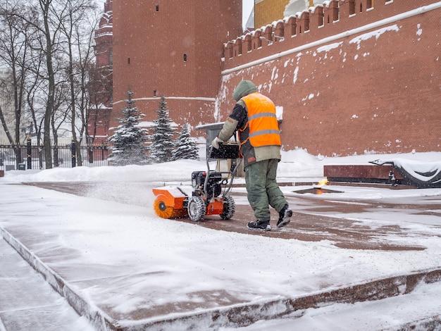 Pracownik komunalny czyści śnieg pługiem śnieżnym przy grobie nieznanego żołnierza na kremlu podczas opadów śniegu. straż honorowa jest na służbie przy wiecznym płomieniu.