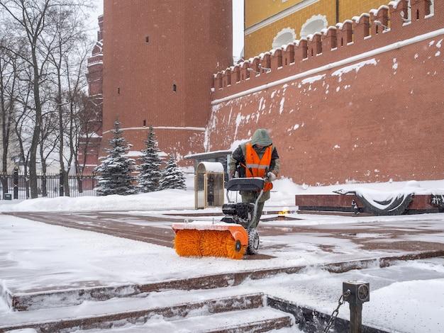 Pracownik komunalny czyści śnieg pługiem śnieżnym przy grobie nieznanego żołnierza na kremlu podczas opadów śniegu