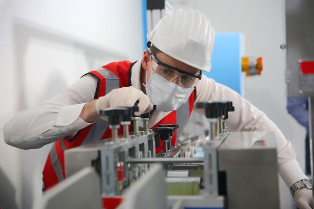 Pracownik kontroli jakości analizujący maszynę produkcyjną w laboratorium.