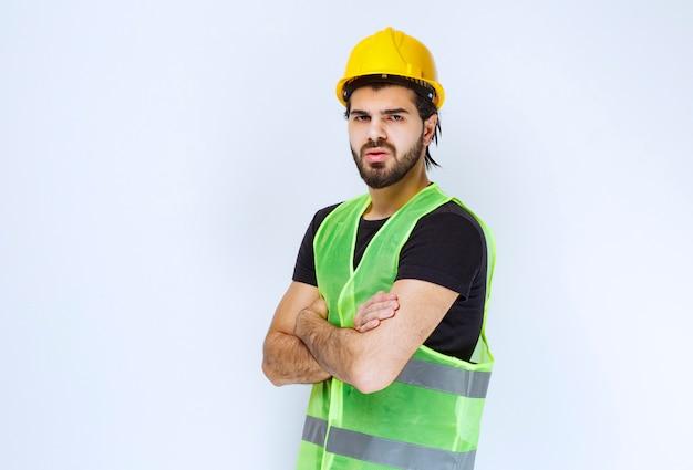 Pracownik krzyżuje ręce i wygląda na niezadowolonego.
