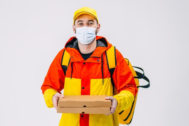 Pracownik kurierski w jednolitej masce z żółtą czapką trzyma kartonowe pudła na białej powierzchni poddanej kwarantannie usługi dostawy