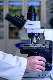 Pracownik laboratorium pracujący z nowoczesnym mikroskopem podczas prowadzenia badań