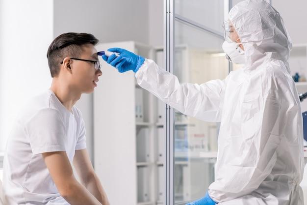 Pracownik laboratorium w kombinezonie ochronnym, masce, rękawiczkach i okularach, podczas badania używa specjalnego narzędzia medycznego