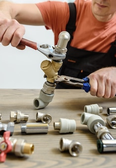 Pracownik łączący elementy instalacji wodociągowej za pomocą kluczy nastawnych