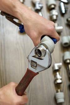 Pracownik łączy elementy hydrauliki za pomocą kluczy nastawnych