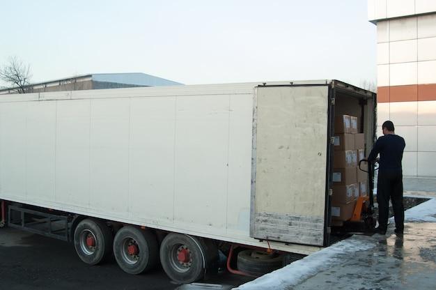 Pracownik ładuje pudła do ciężarówki