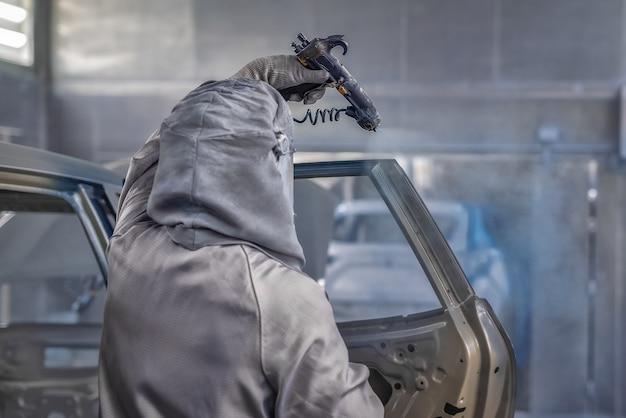 Pracownik lakierni fabryki samochodów maluje elementy samochodu.