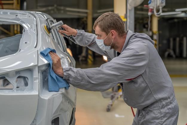 Pracownik lakierni fabryki samochodów poleruje pomalowaną powierzchnię