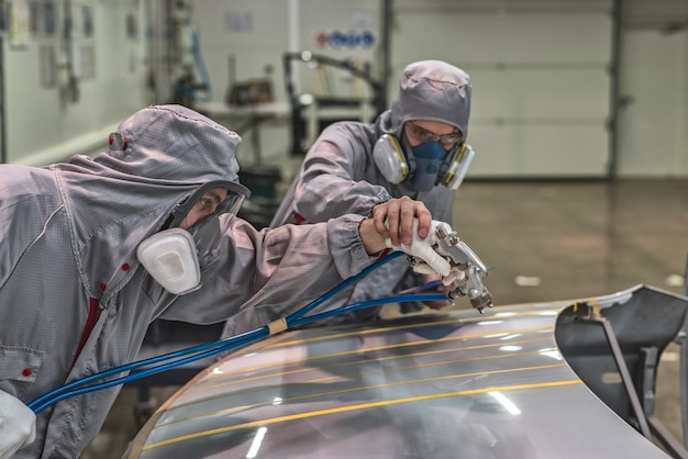 Pracownik lakierni fabryki samochodów prowadzi szkolenia z malowania elementów karoserii