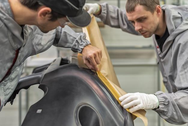 Pracownik lakierni fabryki samochodów prowadzi szkolenie z przygotowania zderzaków do malowania
