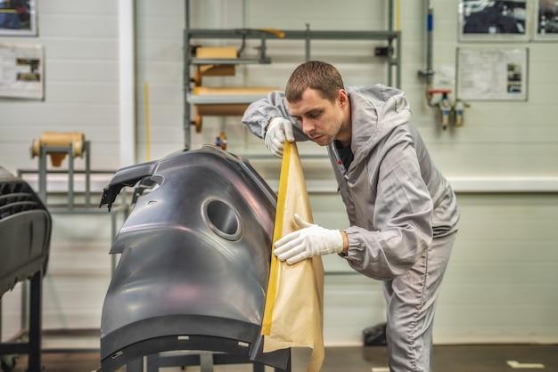 Pracownik lakierni fabryki samochodów przygotowuje zderzaki do malowania