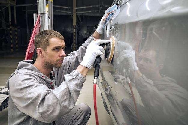 Pracownik lakierni fabryki samochodów szlifuje pomalowaną część narzędziem pneumatycznym.