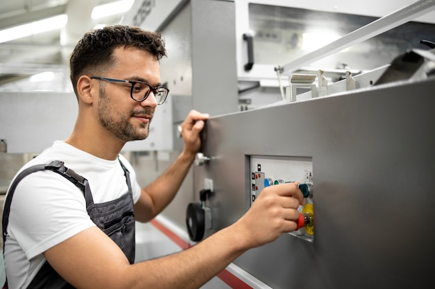 Pracownik linii produkcyjnej w pracy jednolitej działającej maszynie przemysłowej do procesu produkcyjnego