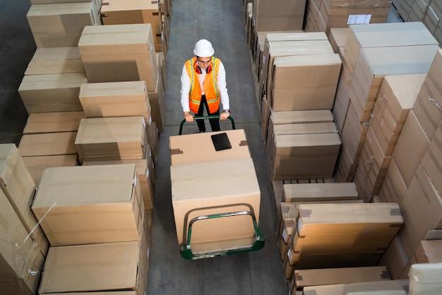 Pracownik logistyki dostarczający pudełka na wózku