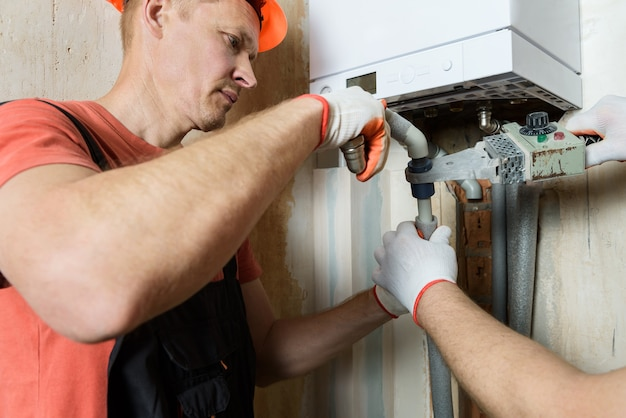 Pracownik lutuje plastikowe rury i podłącza je do domowego kotła gazowego