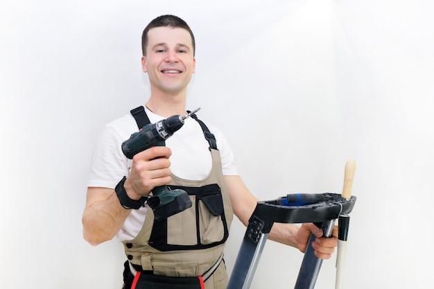 Pracownik ma w rękach śrubokręt. technik w specjalistycznym kombinezonie