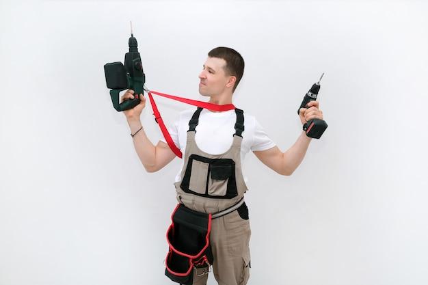 Pracownik ma w rękach wiertarkę udarową i śrubokręt. technik w specjalistycznym kombinezonie