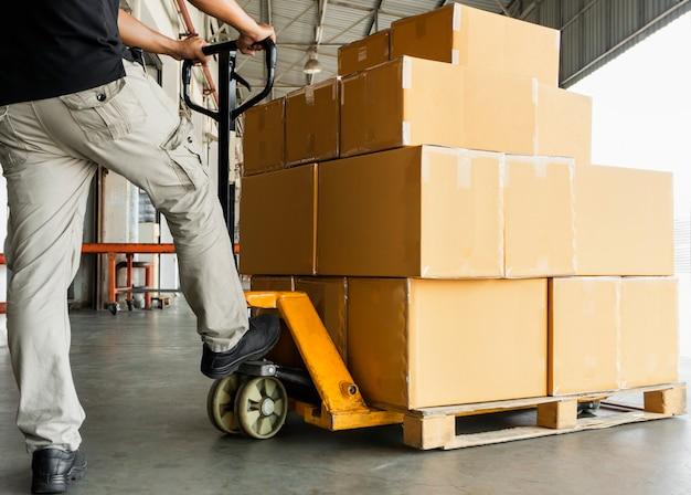 Pracownik magazynu ładuje pudełka wysyłkowe na palecie.