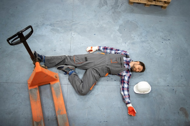 Pracownik magazynu leżący nieprzytomny na betonowej podłodze po upadku