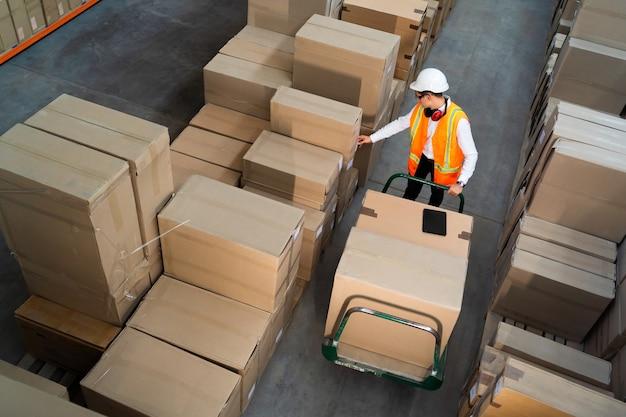 Pracownik magazynu logistycznego dostarczający pudełka