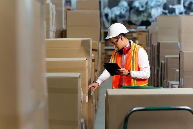 Pracownik magazynu logistycznego prowadzi inwentaryzację produktów