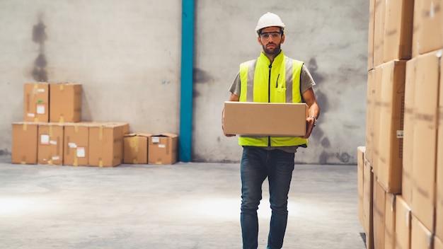 Pracownik magazynu niosący karton w magazynie