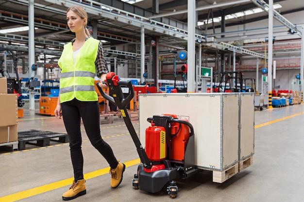 Pracownik magazynu przeciąga ręczny wózek paletowy lub ręczny wózek widłowy z rozładunkiem palety transportowej na ciężarówkę
