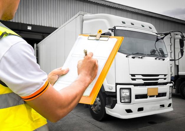 Pracownik magazynu ręka trzyma schowek sprawdzający załadunek kontroli przesyłki ciężarówkami, logistyka transportu towarowego