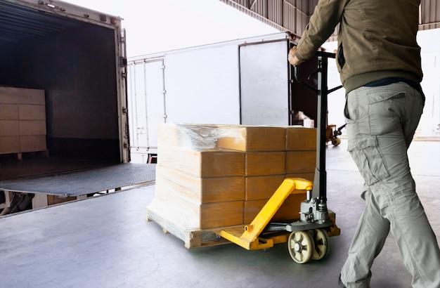 Pracownik magazynu rozładowujący towary z palet na ciężarówkę. dostawa i transport ładunków.