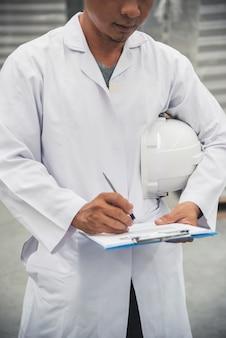 Pracownik magazynu sprawdzanie jego listy w schowku w dużej fabryce magazynu