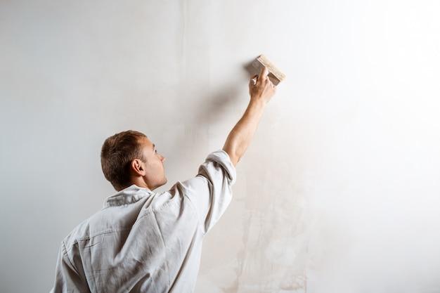 Pracownik malowanie ścian pędzlem w kolorze białym.