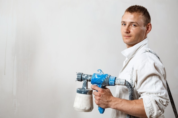 Pracownik malowanie ścian z pistoletu w kolorze białym