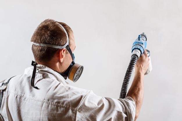 Pracownik malowanie ścian z pistoletu w kolorze białym.