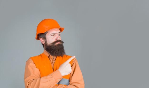 Pracownik mechaniczny wskazuje. reklama. brodaty mężczyzna w kasku budowlanym. brodaty mężczyzna w kasku. biznes, przemysł, technologia. koncepcja konstruktora.