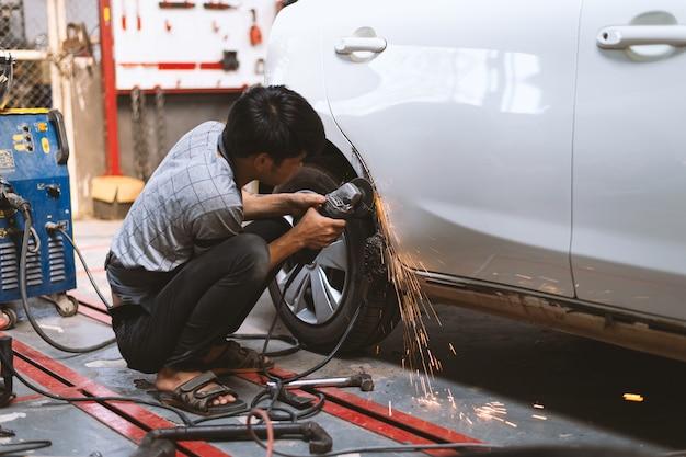 Pracownik mechanika naprawia karoserię i maluje profesjonalną obsługą