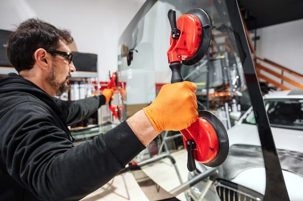 Pracownik mechanika samochodowego podczas wymiany przedniej lub przedniej szyby samochodu w warsztacie samochodowym.