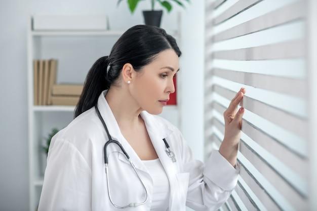 Pracownik medyczny. dorosła smutna kobieta w białym fartuchu ze stetoskopem na szyi, stojąca przy oknie, z ręką przy roletach.